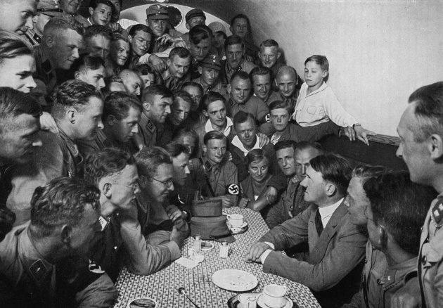 Adolf Hitler sits at a table facing a group of young uniformed National Socialists crowded into a small room in the Braune Haus, Munich (1935)